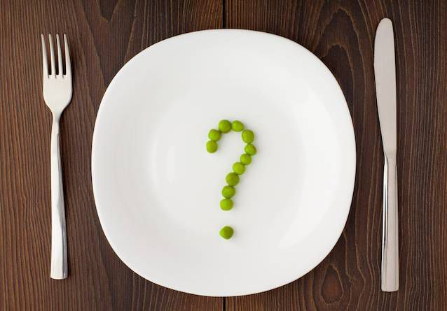 Place setting with beans arranged in a question mark on a white plate