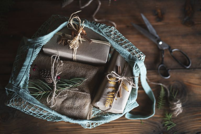 Bag with christmas presents wrapped in brown paper and burlap sitting on a wooden table