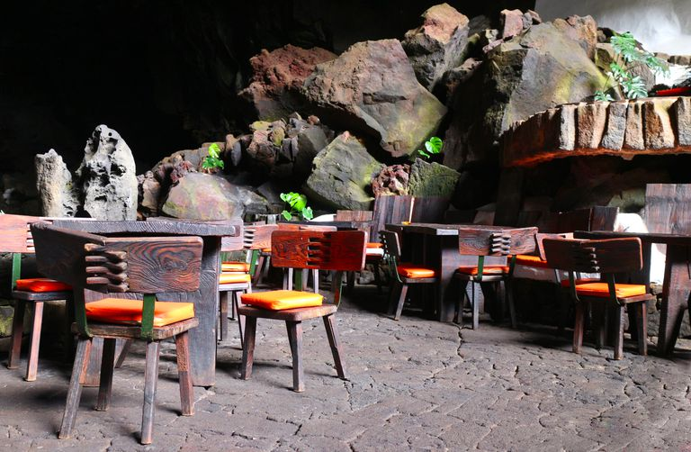 Dining tables in dimly lit volcano cave in Canary Islands