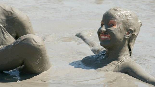 Person lying in a mud bath with mud covering her face and hair