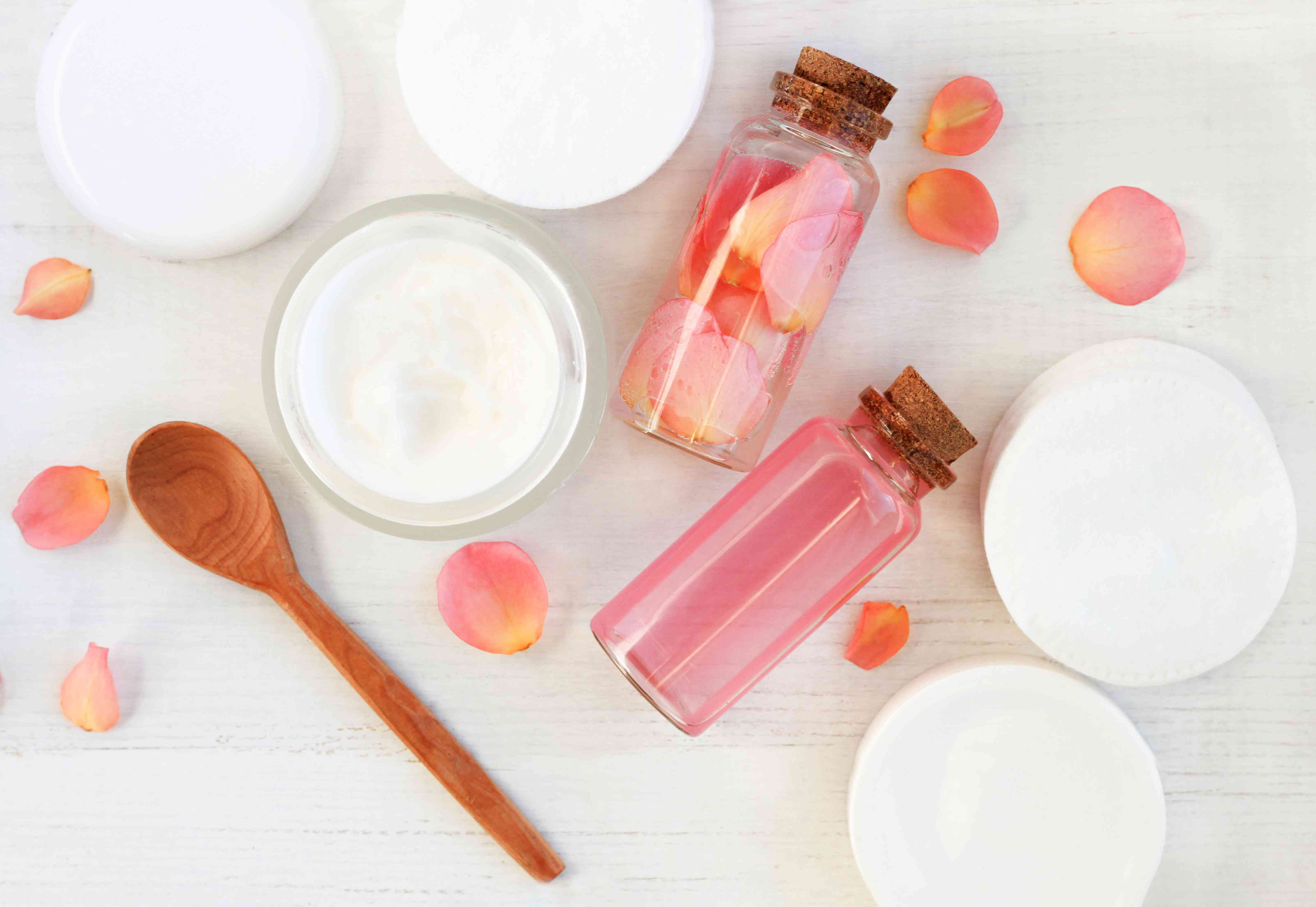 Two bottles of rosewater are lying on a pale wooden surface, with a wooden spoon, five bowls of white cream and some rose petals around them
