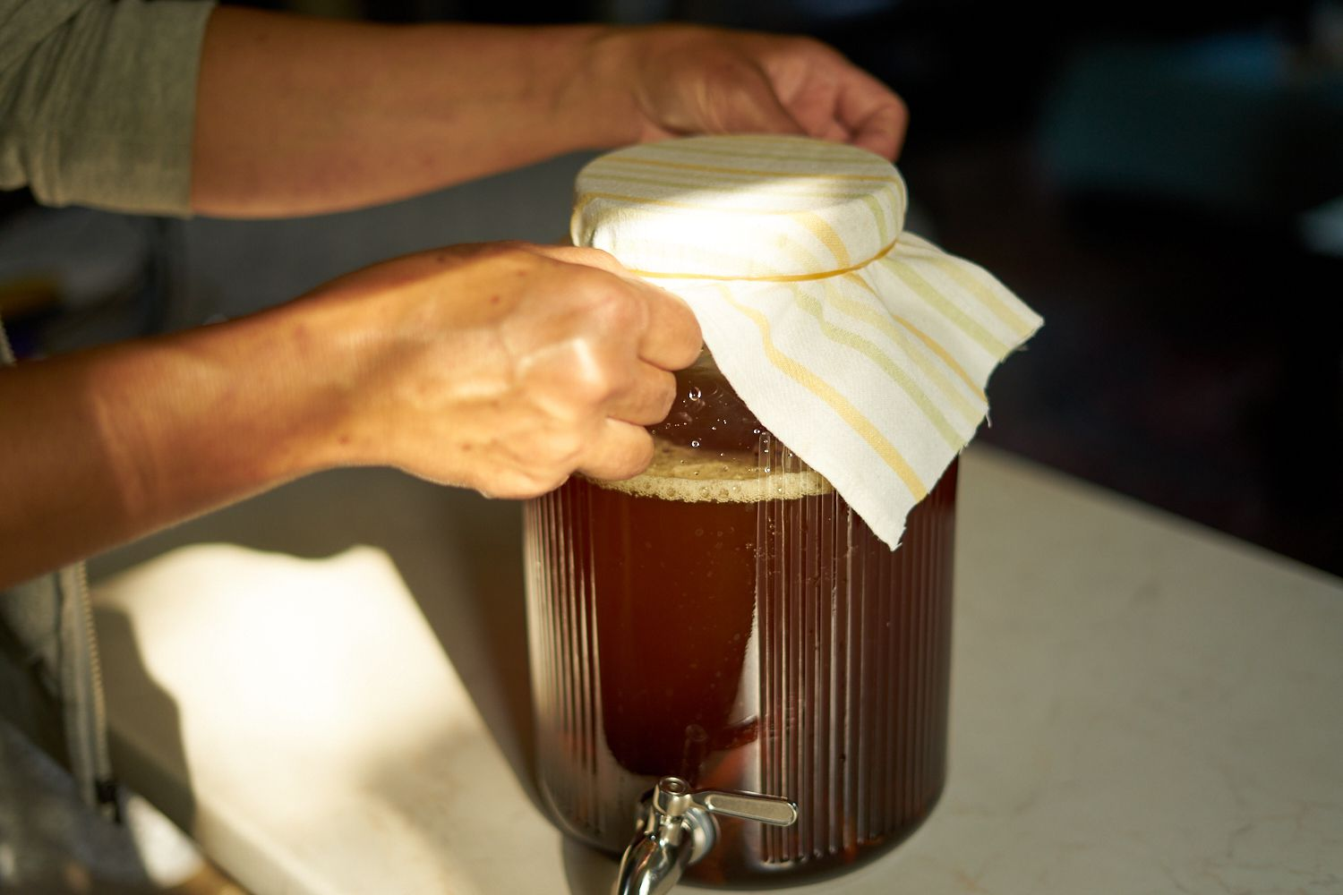 hands put cheesecloth covering, secured with rubber band, on large glass dispenser for kombucha fermentation