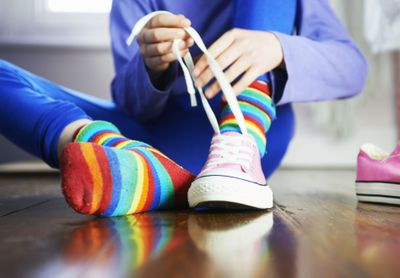 young child tying shoe laces with colourful socks