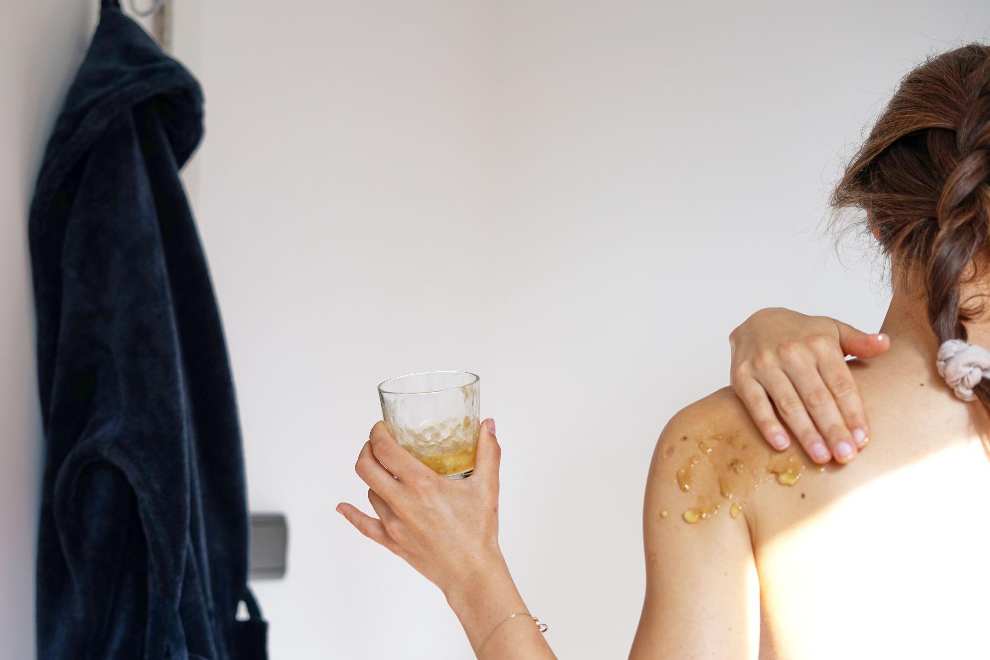 back shot of woman rubbing diy homemade banana sugar scrub into her shoulders