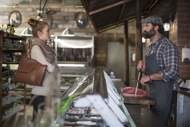 A woman with crossed arms talking to a butcher.
