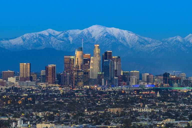 The snow-capped peaks of San Gabriel Mountains National Monument rise above the skyline of downtown Los Angeles