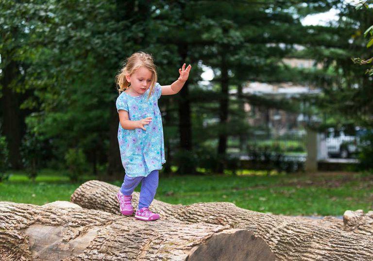 A girl runs across a log