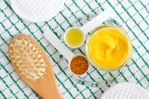 Hairbrush and turmeric face mask ingredients on a checkered cloth
