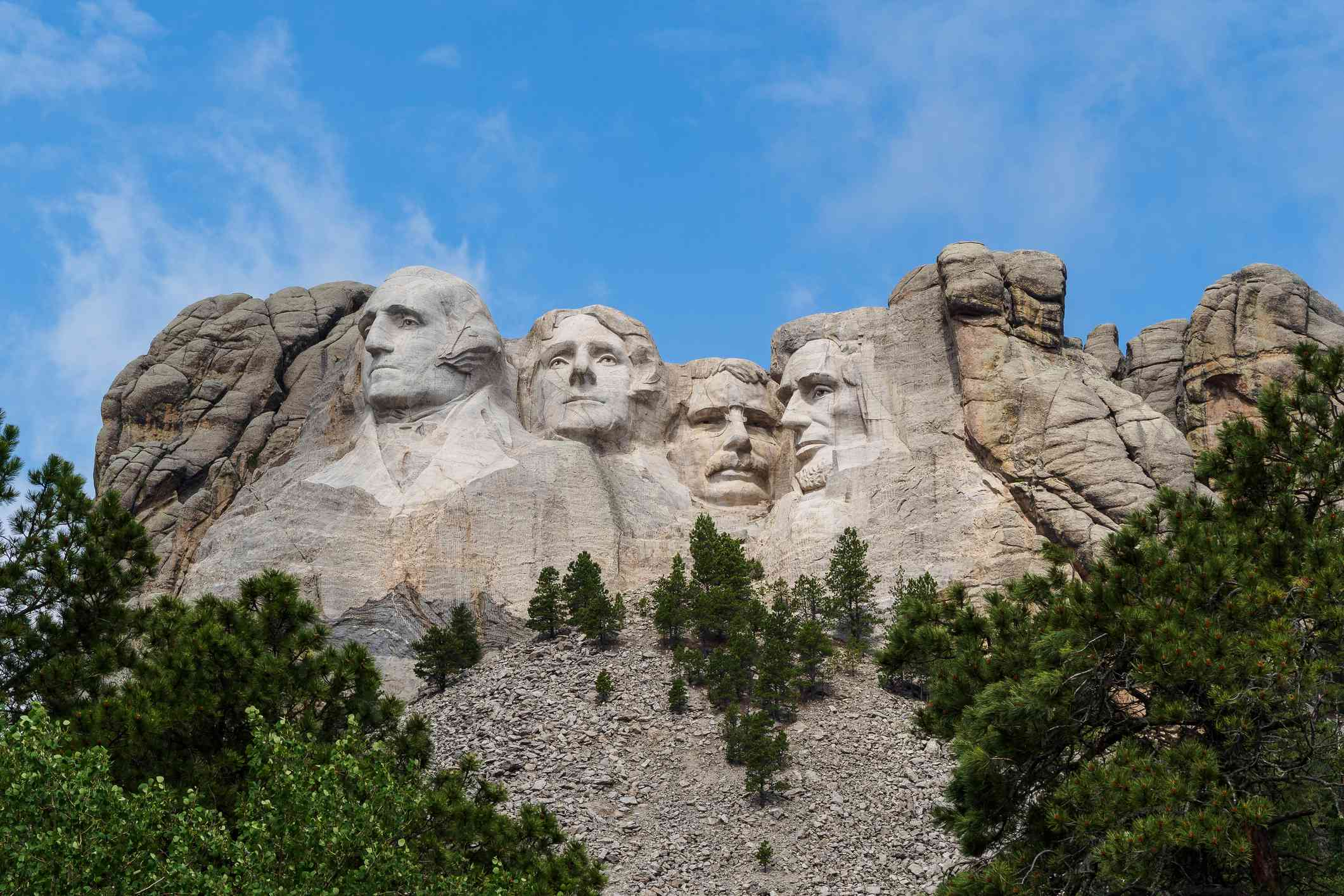 The faces of four past US Presidents carved on a granite face of Mount Rushmore in the Black Hills in Keystone, South Dakota with blue skies and light white clouds above