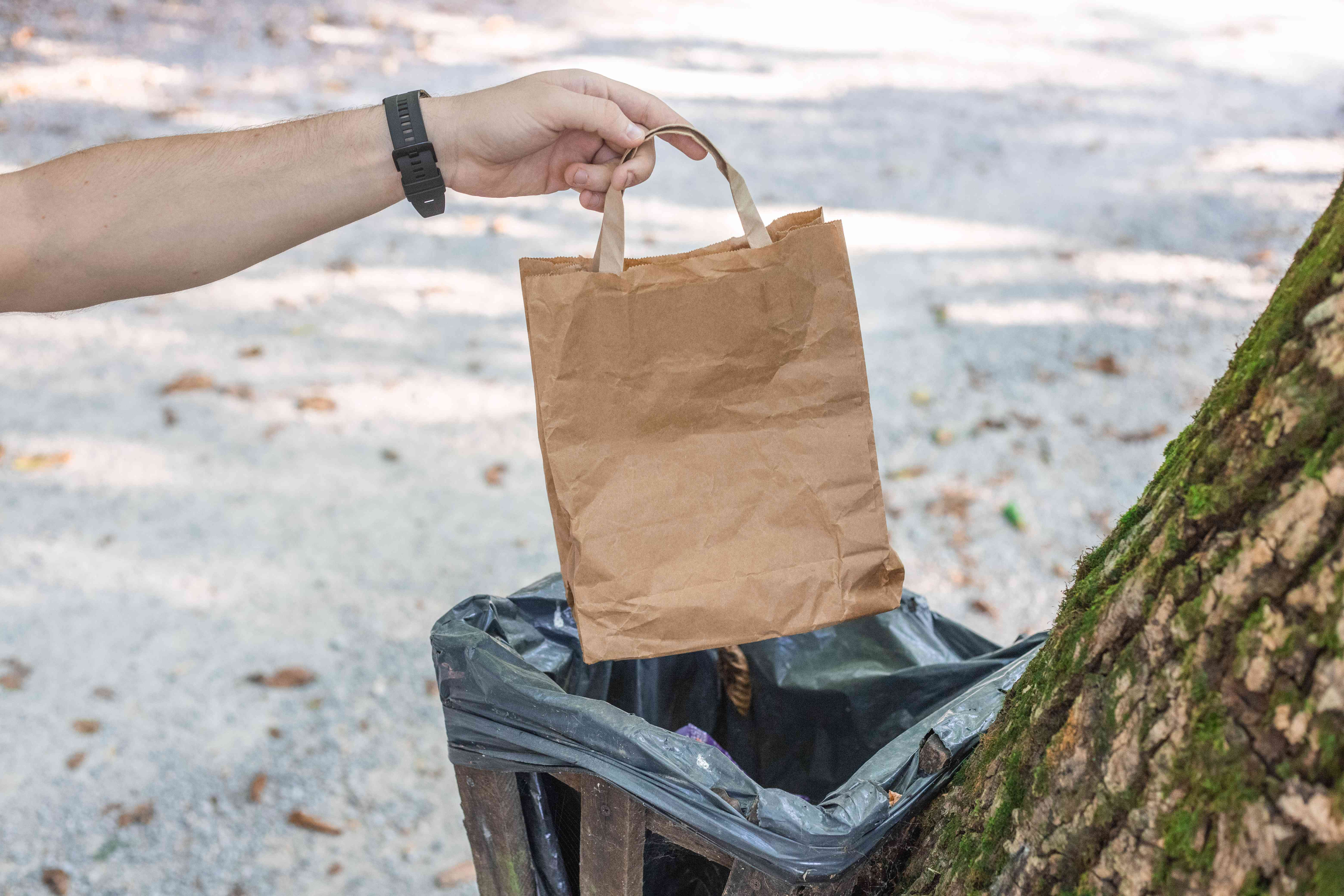 hiker tosses brown paper bag into campsite's trash can