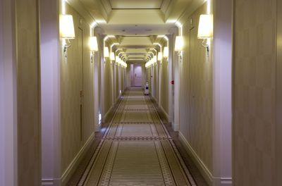 A long beige hotel or apartment hallway with several doors on either side
