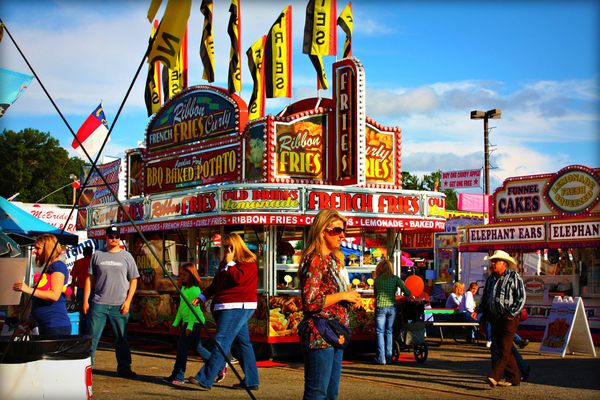 Brightly colored image of people at a far or carnival