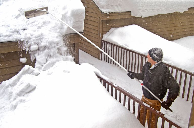 Man clearing snow from roof