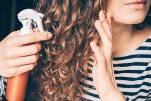 Woman applying spray on curly brown hair