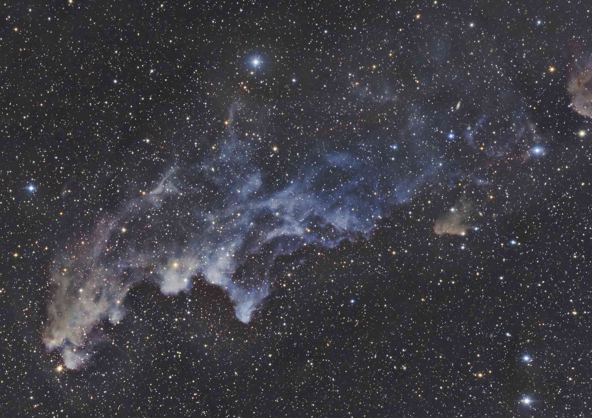 night sky showing Witch Head Nebula, Orion amid a dark sky filled with stars