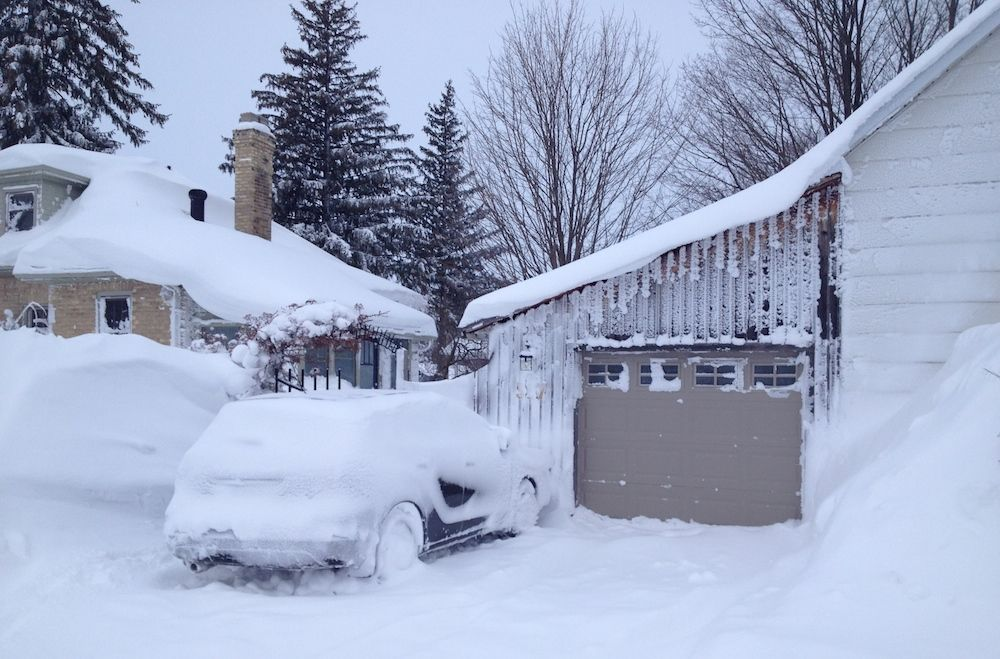 House and car covered in snow after a winter storm