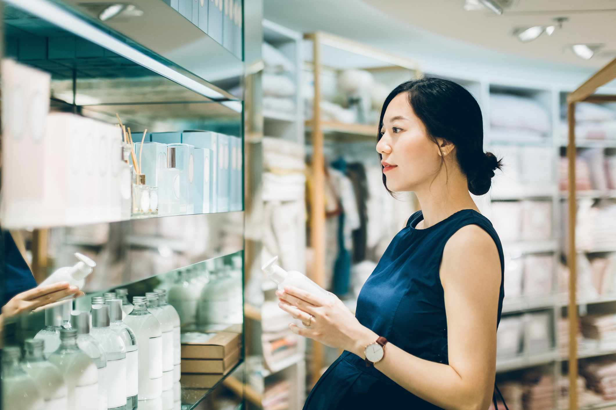 A pregnant Asian woman looks at cosmetics on a shelf at the store.
