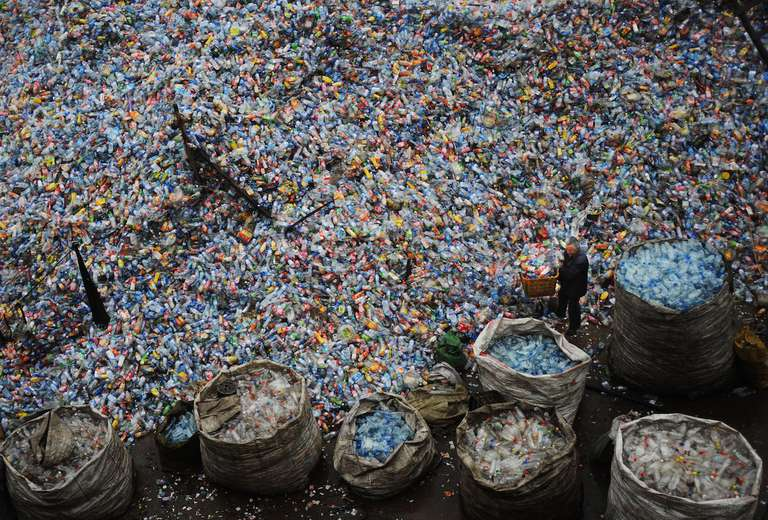 A worker sorts used plastic bottles at a plastics recycling mill