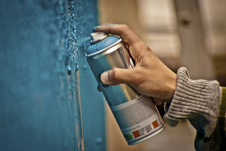 Person spray painting a surface blue