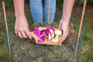 woman in jeans leans over to put food scraps into diy hot compost pile