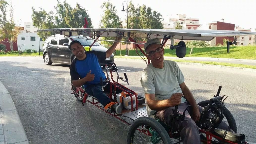Men riding a tandem tricycle