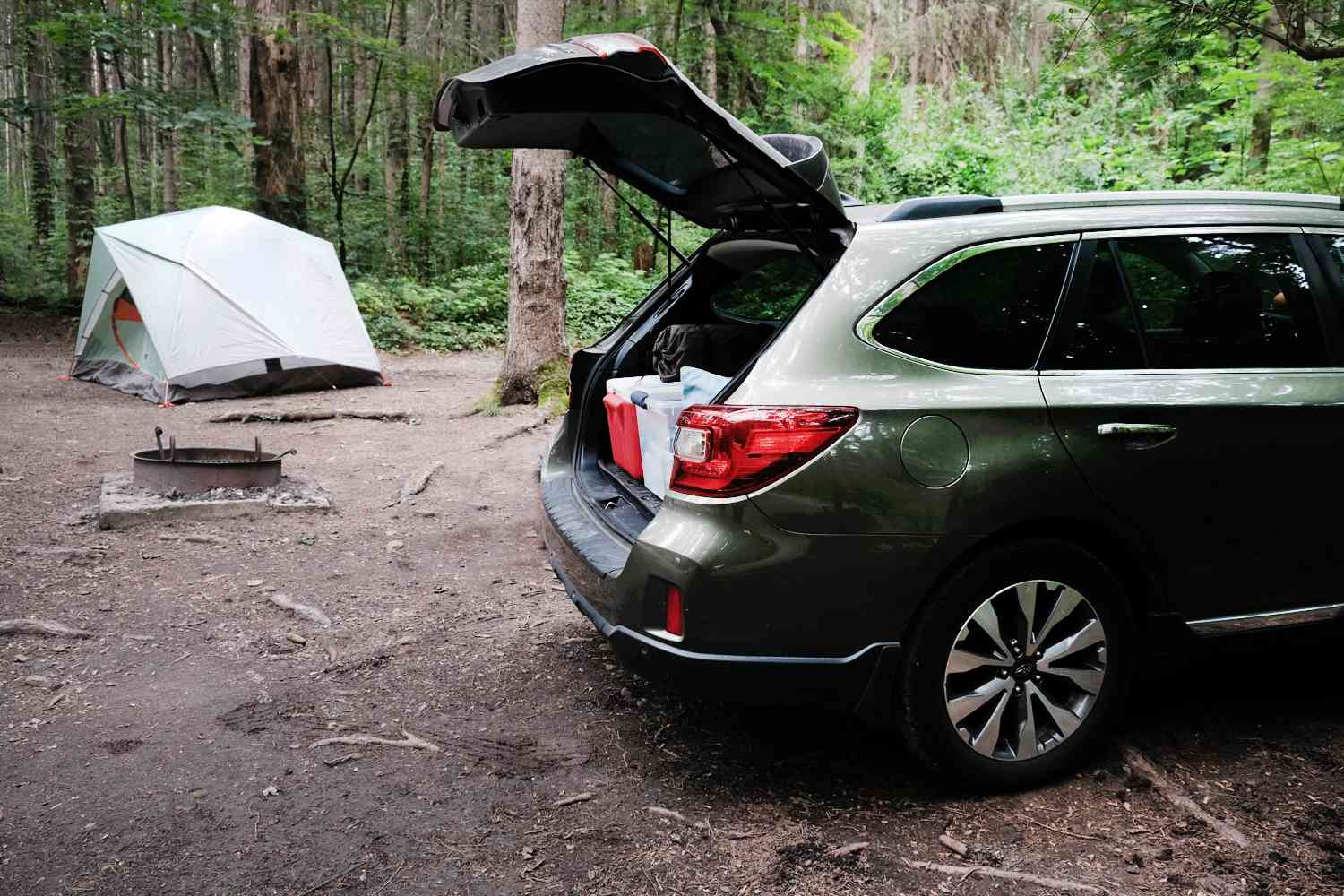 SUV with hatchback popped with camping tent in background nestled in woods