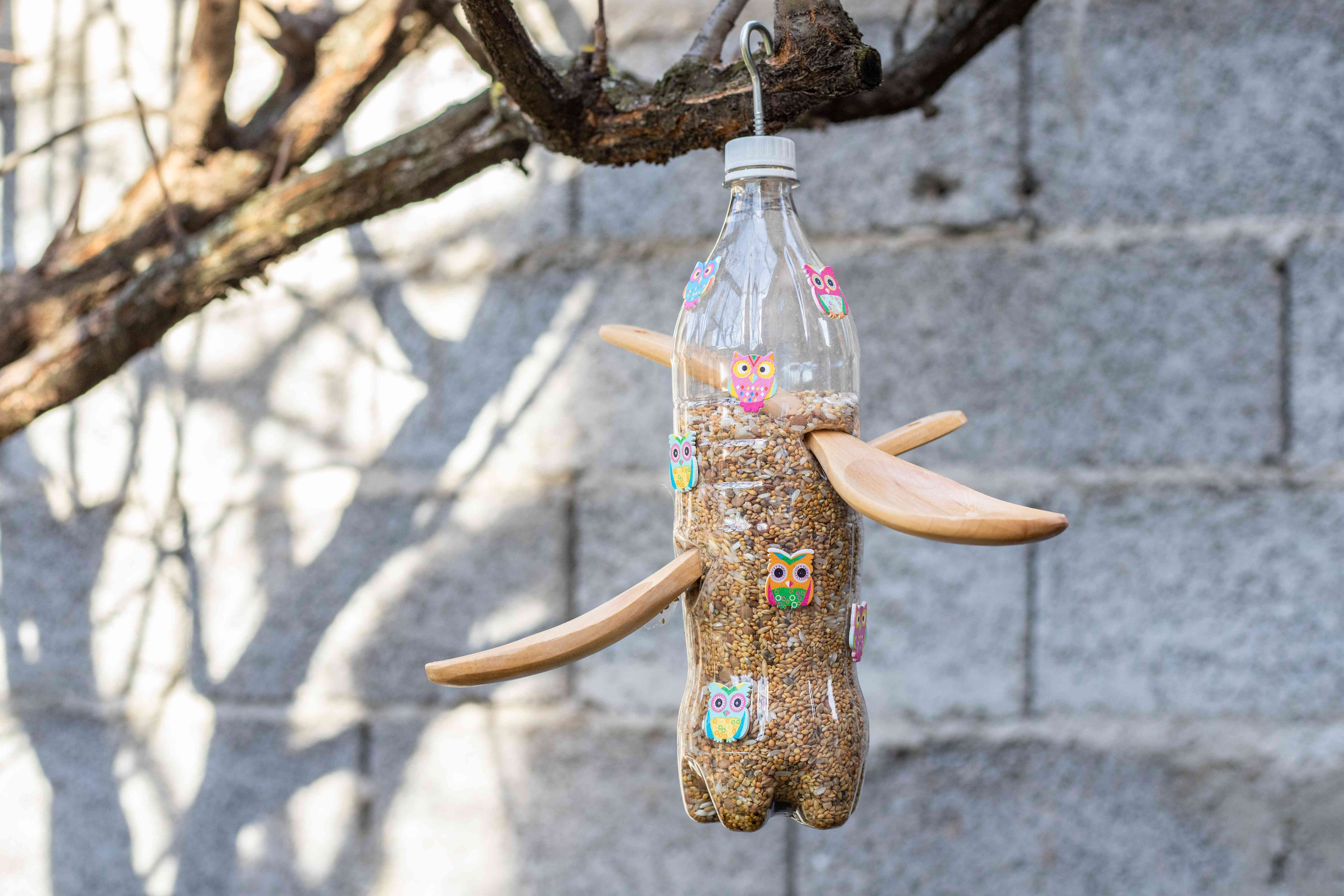 recycled plastic water bottle as bird feeder with wooden spoons