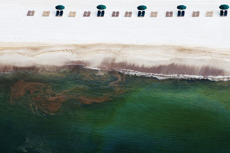 Empty beach chairs rest in the sand as oil washes ashore