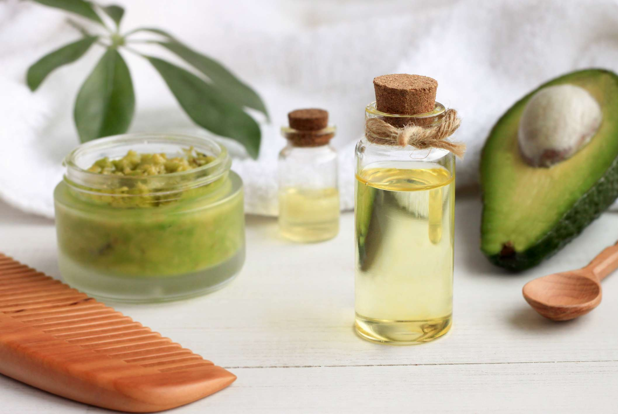 Avocado, jars of oil, and homemade face mask