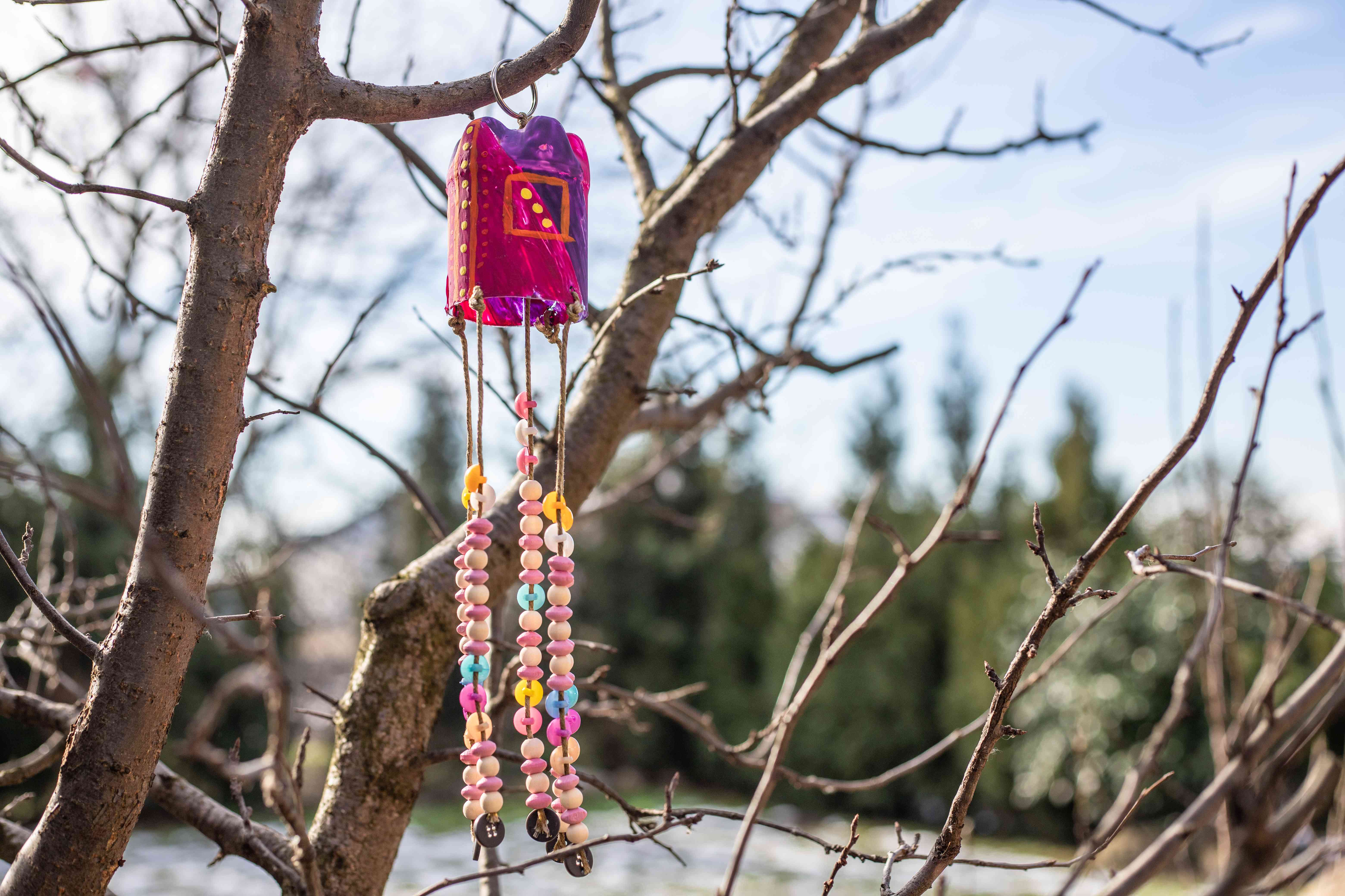recycled plastic bottle as wind chime hung in tree