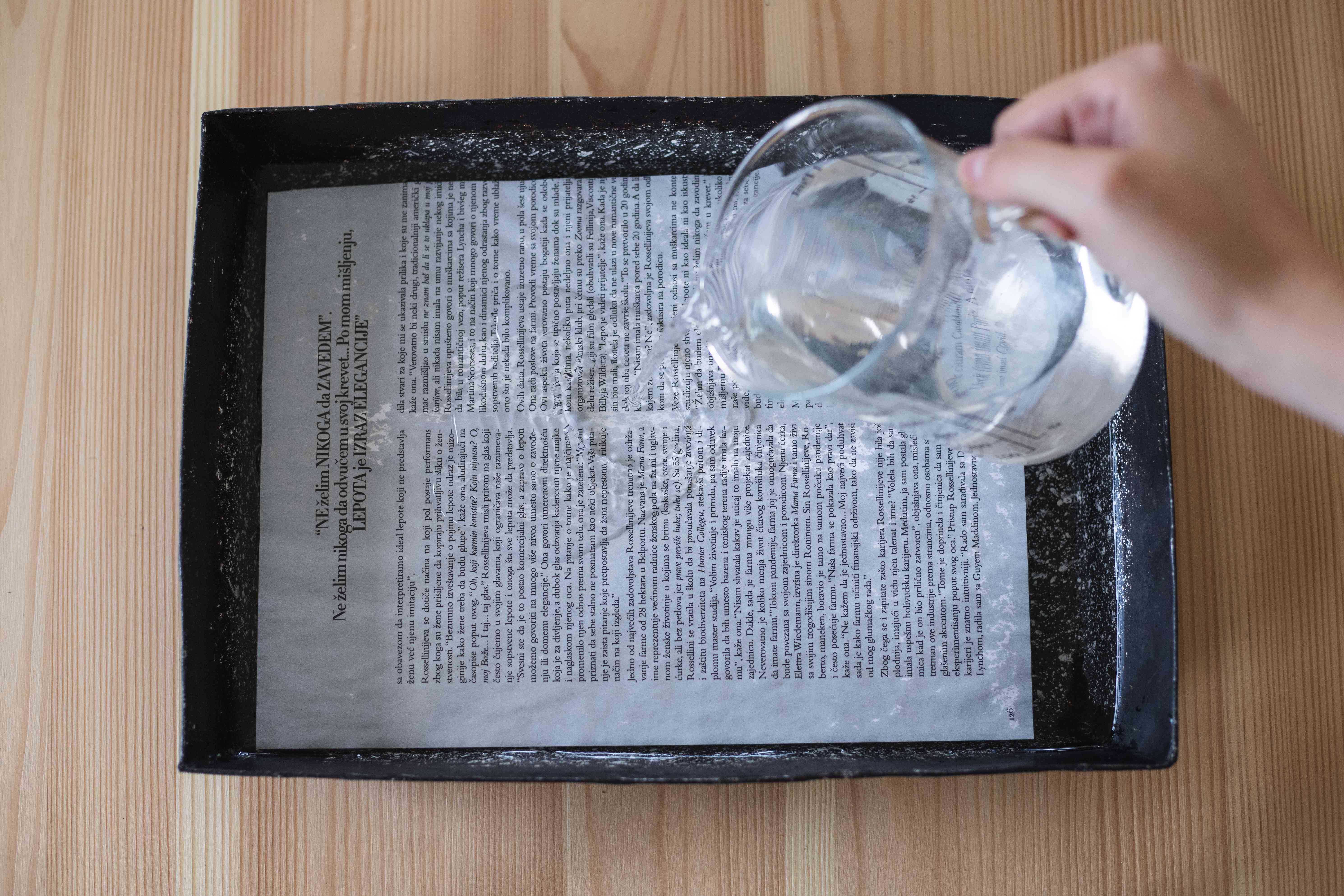 hand pours water on magazine page in tray to make sure it recycles