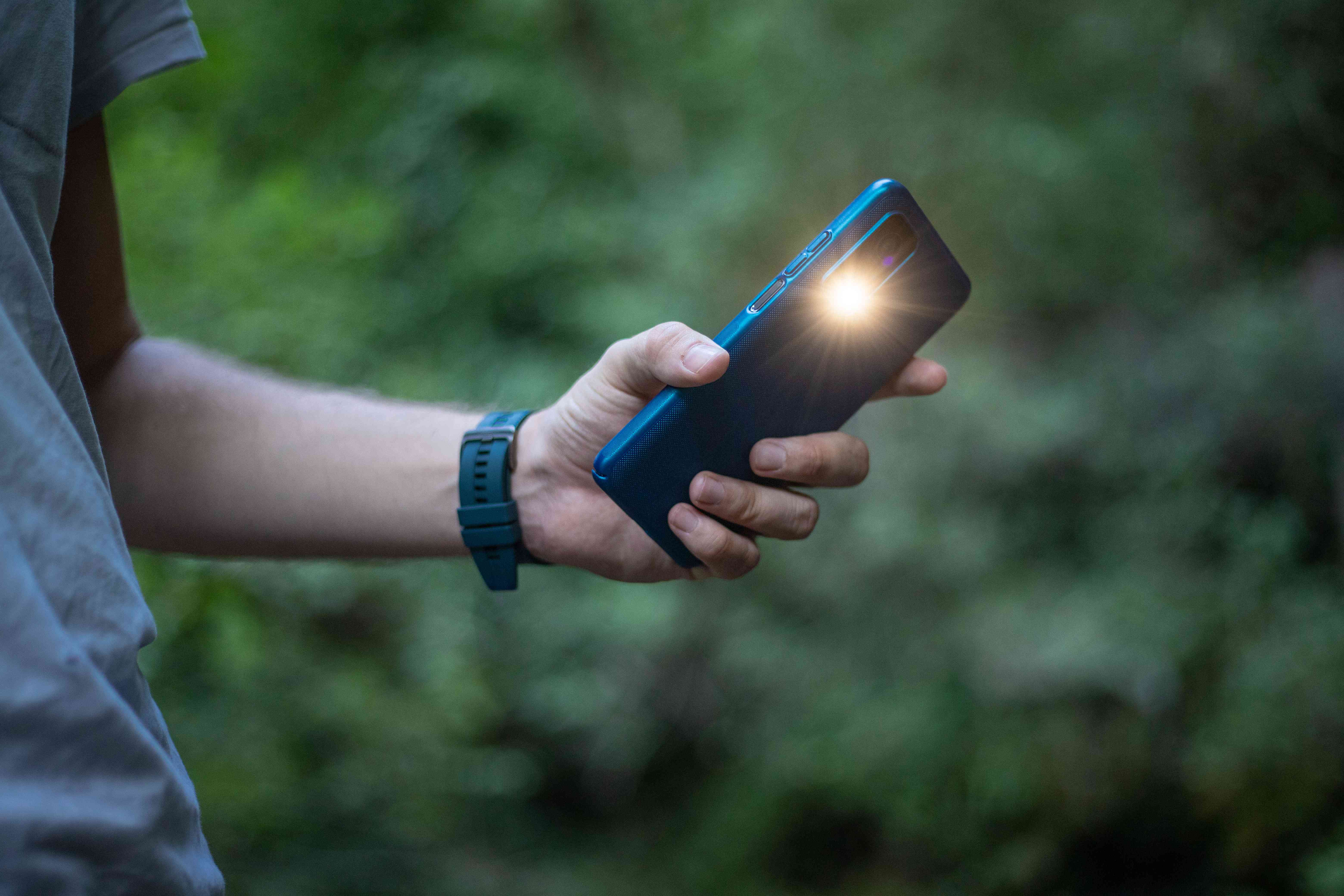 guy uses phone flash light while hiking outside on trail