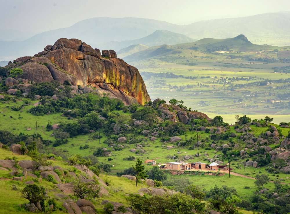 A large rock formation rises above a lush valley of green in Eswatini