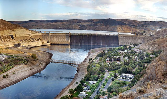 Surrounded mostly by a rocky and barren landscape, the Grand Coulee Dam holds back water on the Columbia Driver on a bright day