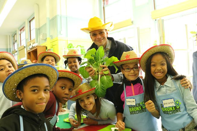 Stephen Ritz holds up a plant grown by students