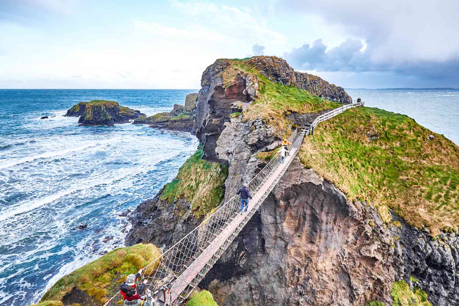 A suspended bridge connects to a small rocky island by the ocean