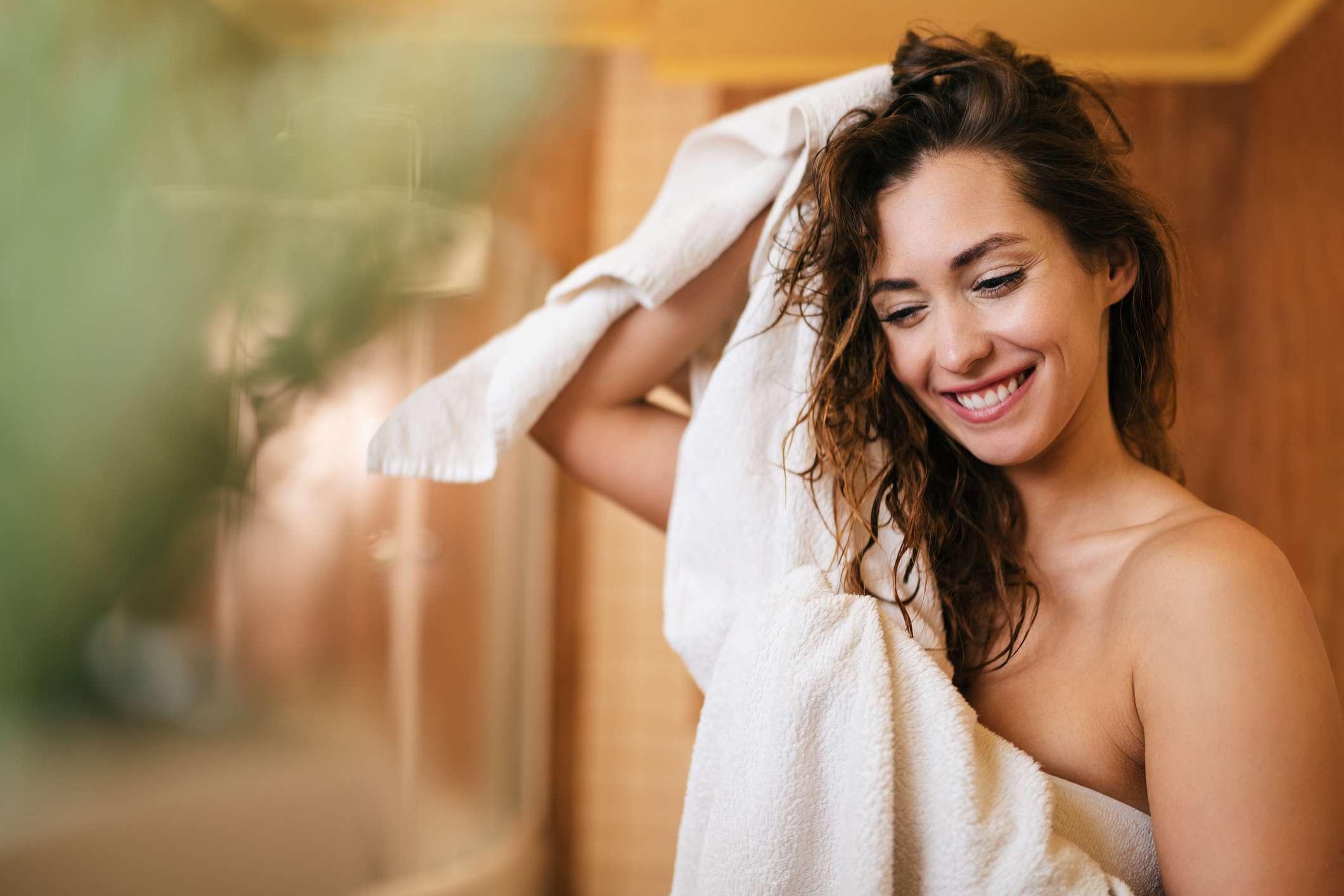 A white woman towel dries her hair.