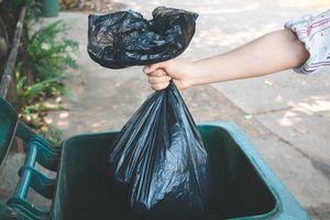 Throwing away a black trash bag