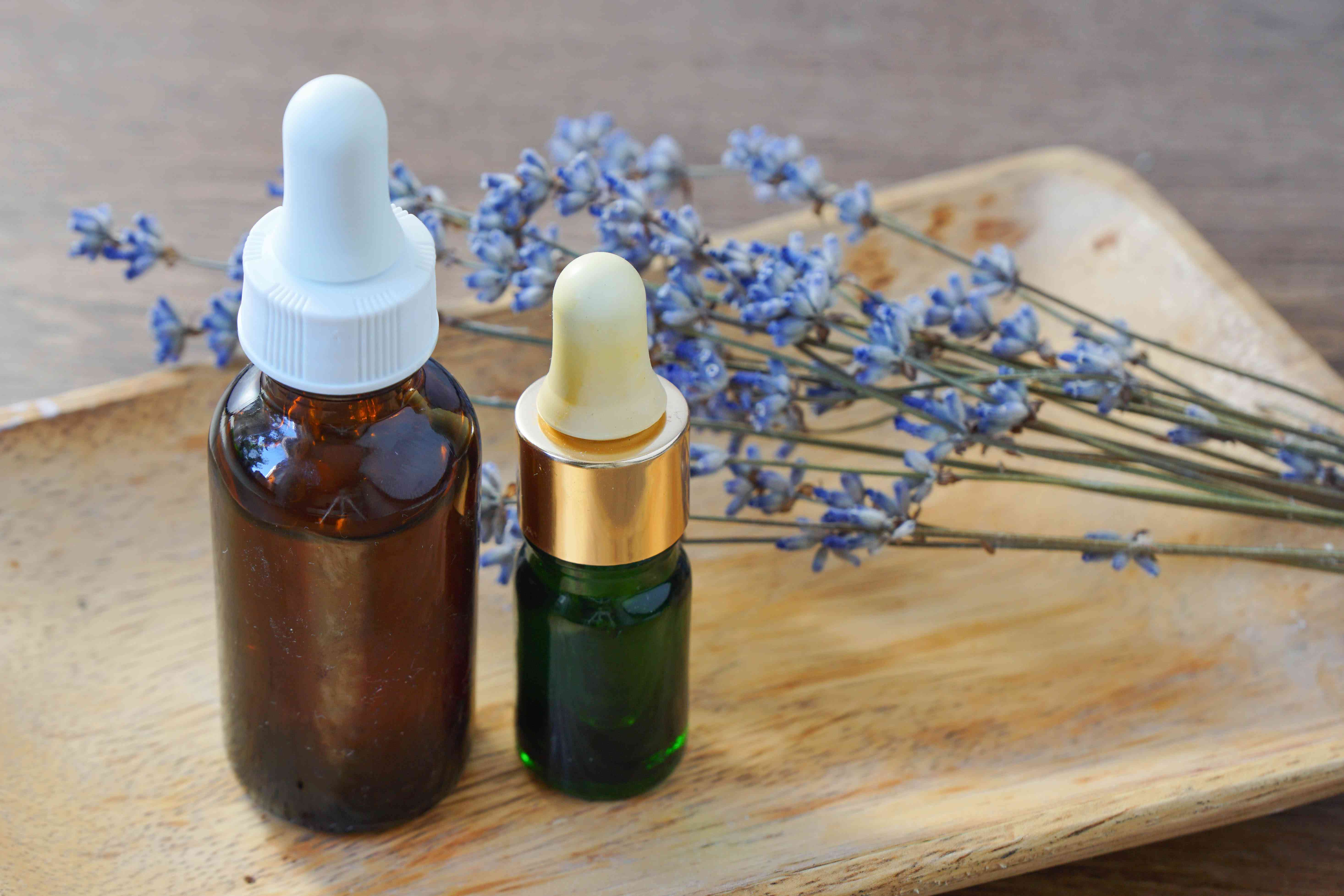 two glass dropper bottles of essential oils next to dried lavender on wooden tray