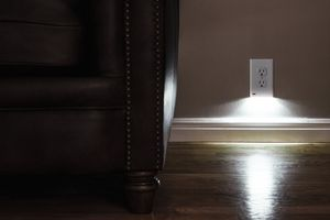SnapRay outlet cover on an outlet next to a leather sofa