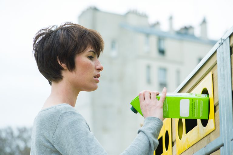 Woman recycling milk carton