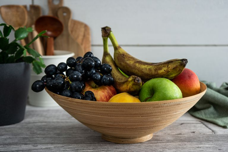 bowl of fruit in kitchen with wooden tools