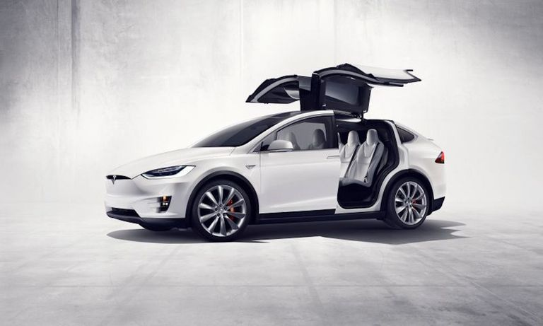 """White Tesla car with """"winged"""" doors open"""