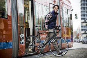 A man exits a city bus walking a bike by his side
