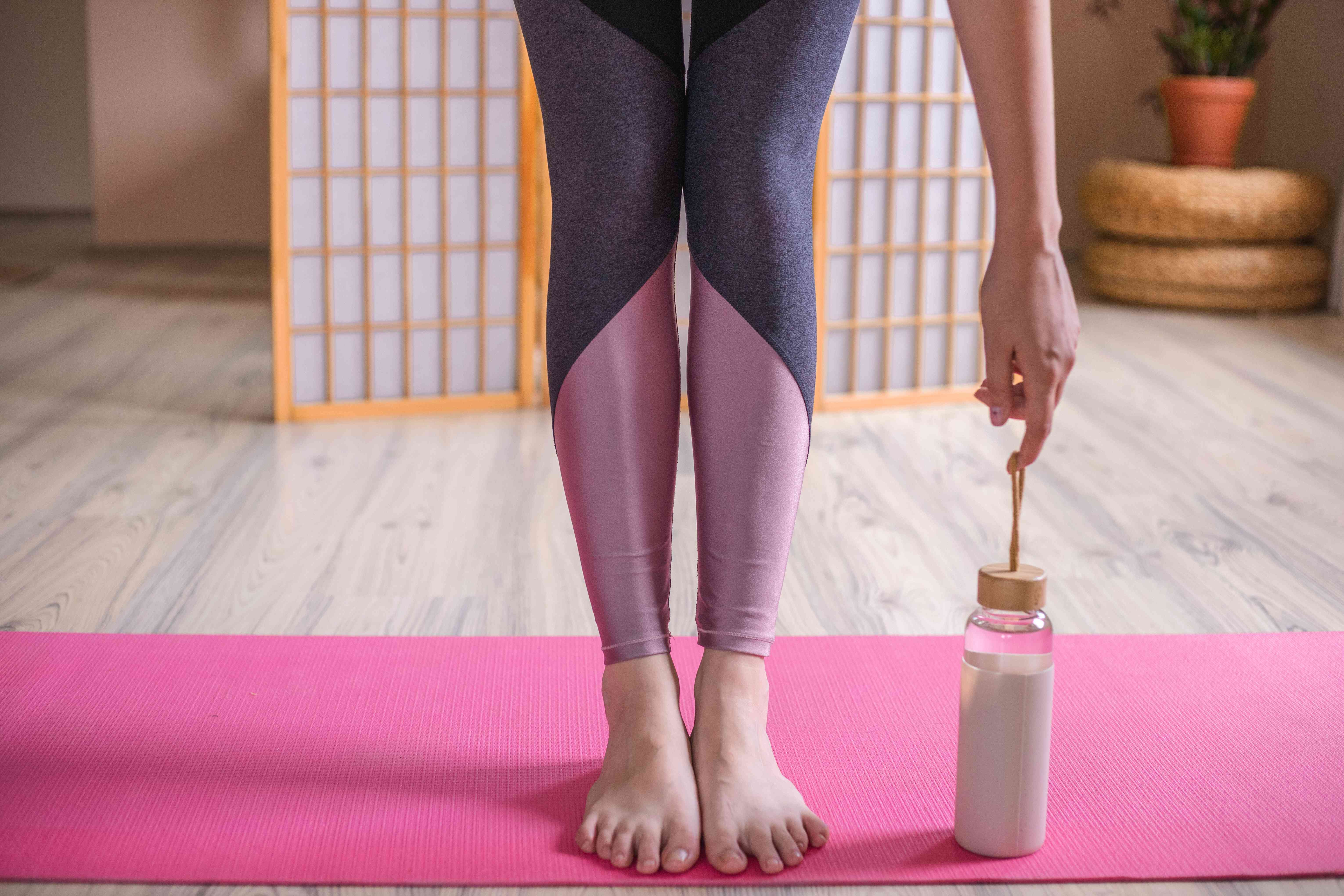 person wearing color-blocked leggings bends forward on pink yoga mat with glass water bottle