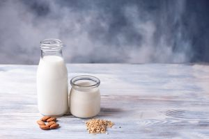 Glass bottles of almond and oat milk on wooden table
