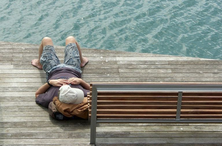person sleeping on then end of a dock