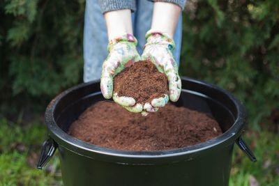 person with garden gloves holds out handful of compost soil over a compost bucket