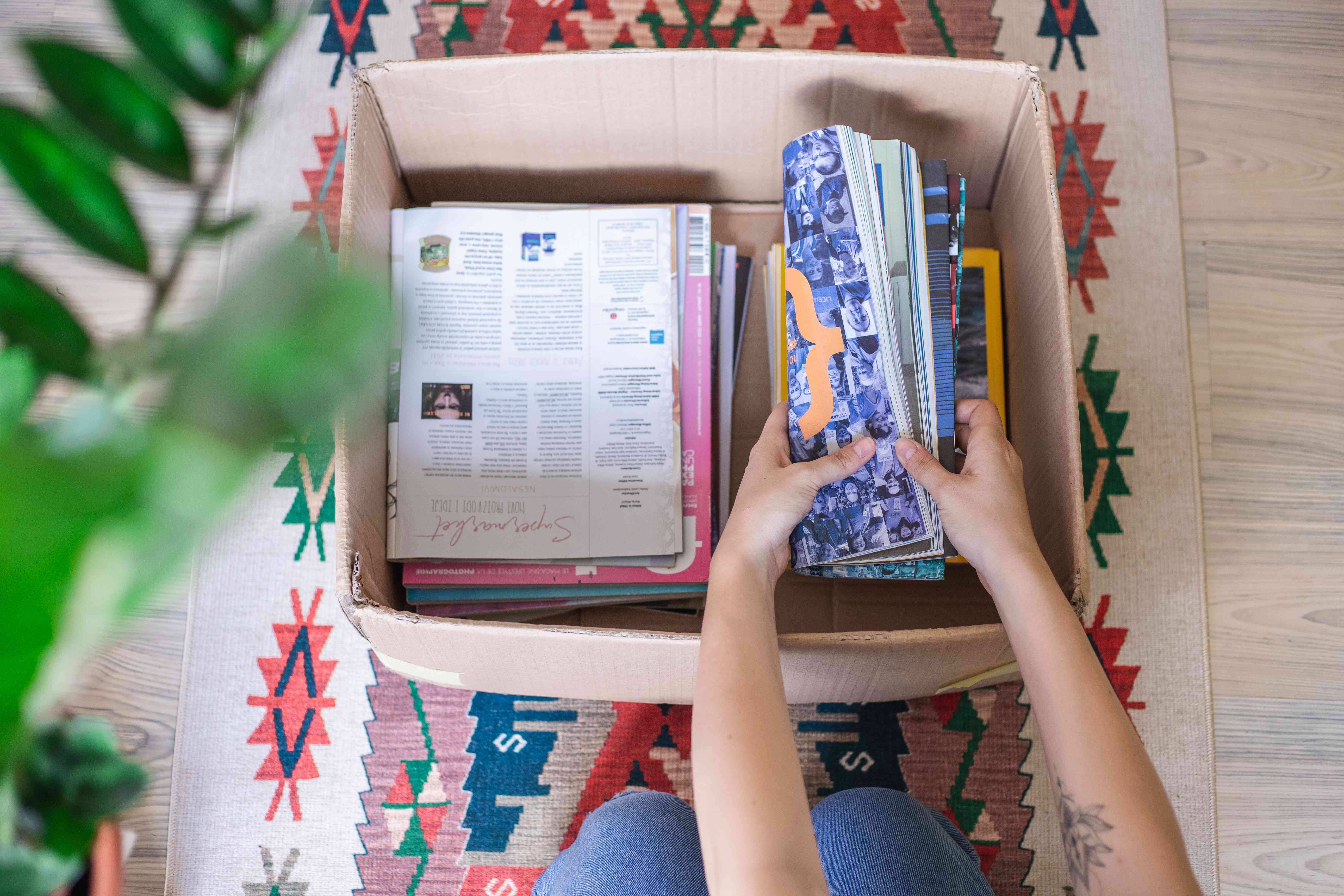 person crouched over cardboard box full of magazines to recycle