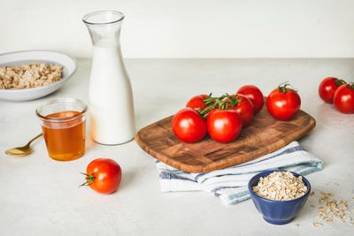 honey, pitcher of milk, tomatoes, and rolled oats are all natural facial cleansers